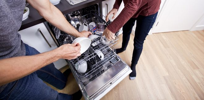couple loading dishwasher together in kitchen