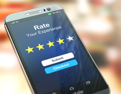 Smartphone or mobile phone with text rate your experience on the screen. Online feedback rating